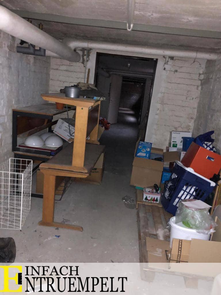 Das Bild zeigt einen Keller mit Sperrmüll, sowie zwei Tischen aufeinander gestapelt. Der Keller hat weiße Putz Wände. Man kann hinter dem Sperrmüll weitere Räume des Kellers erkennen.