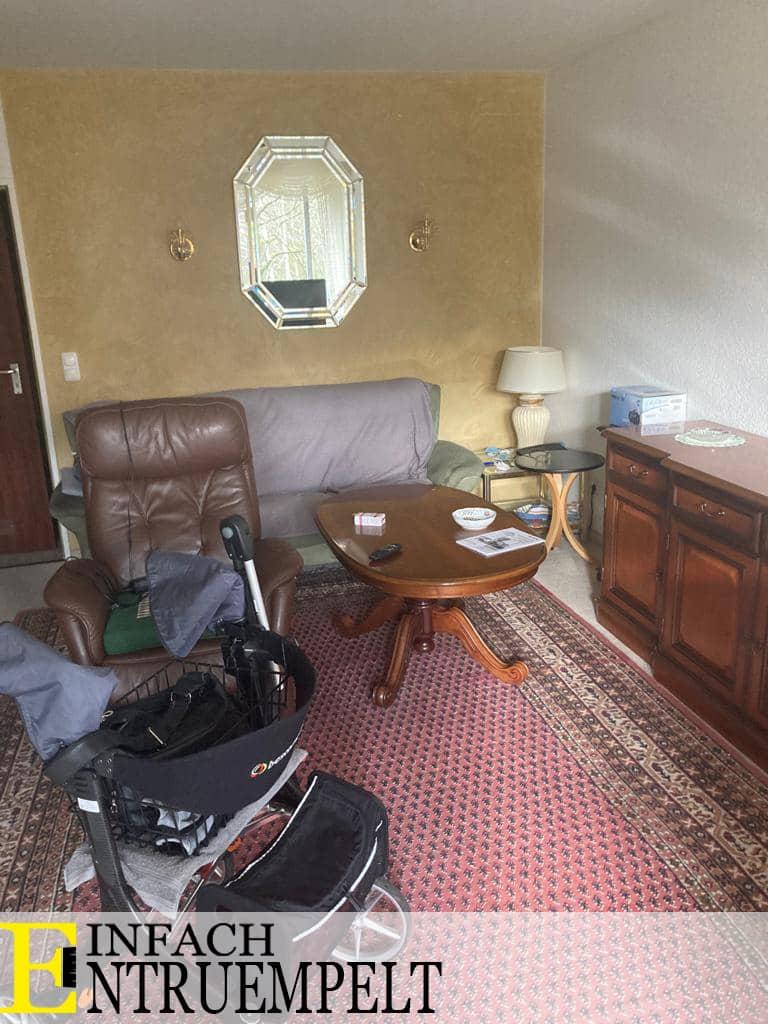 Entruempelung eines Wohnzimmers in Toenisvorst. Es ist ein Wohnzimmertisch, sowie eine Couch zu sehen. Ein großer Teppich auf dem Boden wird von Einfach-Entruempelt ebenfalls entruempelt.